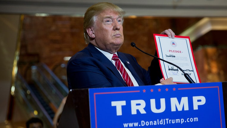 Donald Trump holds up a pledge letter during a news conference at Trump Towers in New York, U.S., on Thursday, Sept. 3, 2015. (Victor J. Blue/Bloomberg via Getty Images)