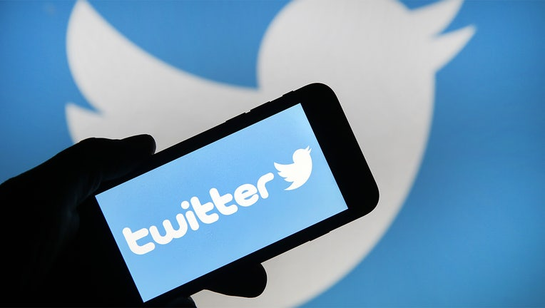 In this photo illustration the Twitter logo is displayed on the screen of an iPhone in front of a computer screen displaying a Twitter logo. (Photo by Chesnot/Getty Images)