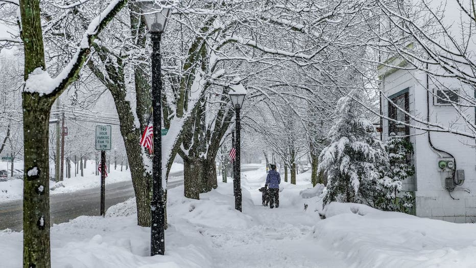 A woman walks her dog on a snow-covered sidewalk in Milford, Pennsylvania.