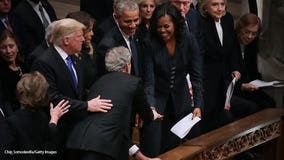 Sweet gesture: George W. Bush hands Michelle Obama a piece of candy at his father's funeral