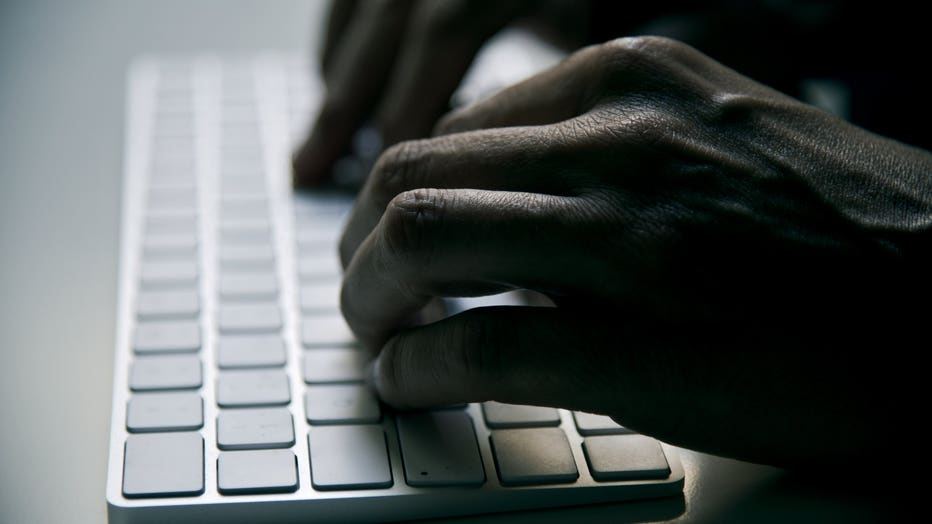 young man typing in a computer keyboard