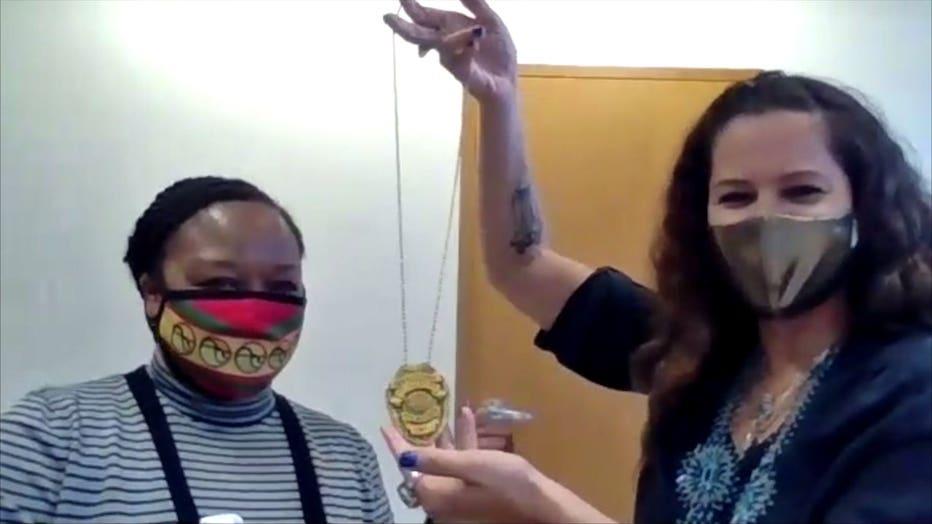 Marlaina Jackson (L) receives a badge from Jeanette Kowalik (R)
