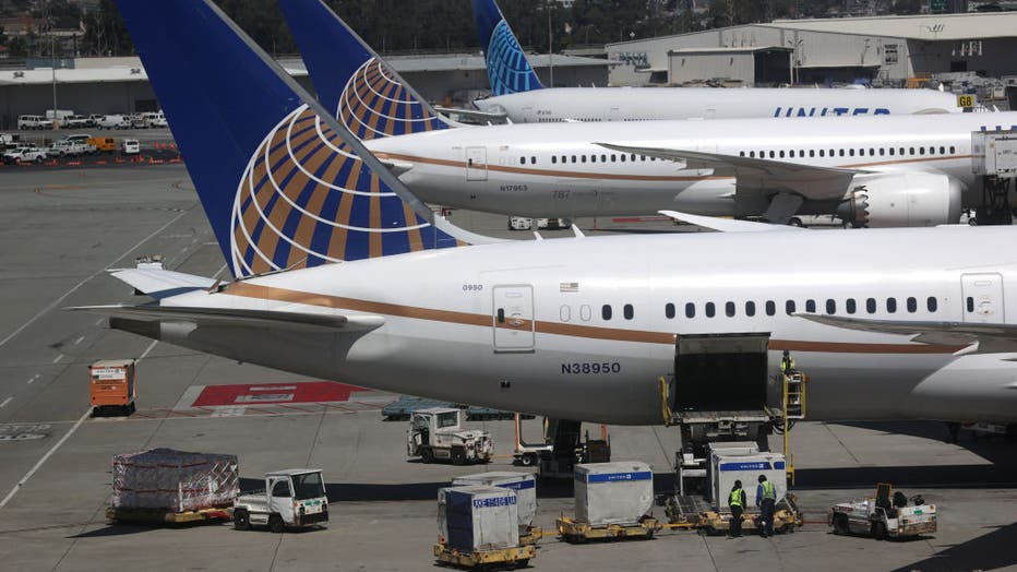 United Airlines workers load cargo onto a plane at San Francisco International Airport on July 08, 2020 in San Francisco, California. (Photo by Justin Sullivan/Getty Images)