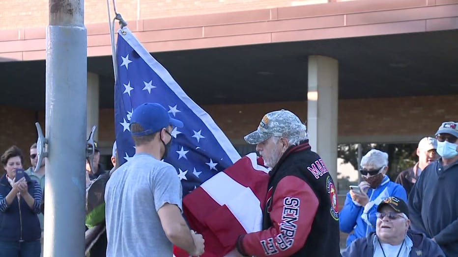 Military veterans replace a flag at Longfellow Middle School that had been taken down amid protests