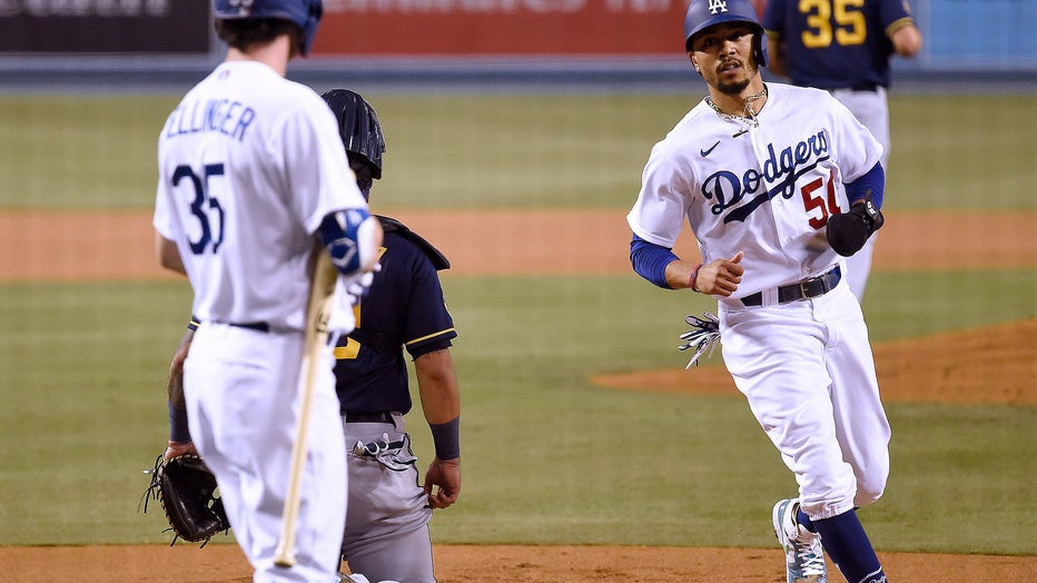 LOS ANGELES, CALIFORNIA - SEPTEMBER 30: Mookie Betts #50 of the Los Angeles Dodgers scores his run in front of Cody Bellinger #35 past Omar Narvaez #10 and Brent Suter #35 of the Milwaukee Brewers, from a Will Smith #16 walk, to take a 1-0 lead during the first inning in game one of the National League Wild Card Series at Dodger Stadium on September 30, 2020 in Los Angeles, California. (Photo by Harry How/Getty Images)