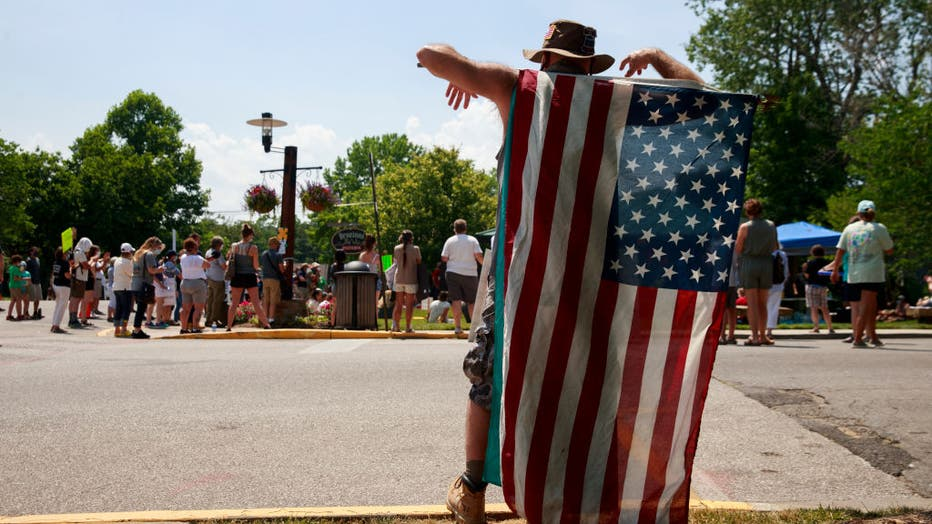 A man holds an American flag during the demonstration.