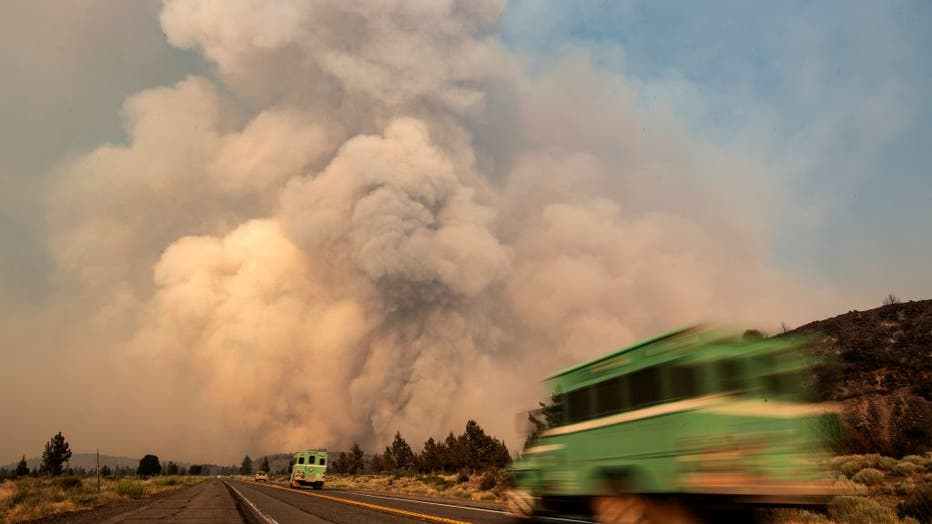 FILE - Firefighters head towards the Lava fire as it sends huge ash plumes into the sky in Weed, California on July 1, 2021.(Photo by JOSH EDELSON/AFP via Getty Images)