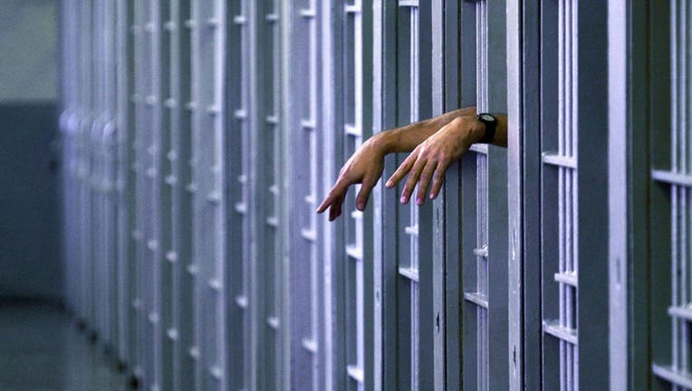An inmate's hands peer out from inside a jail cell