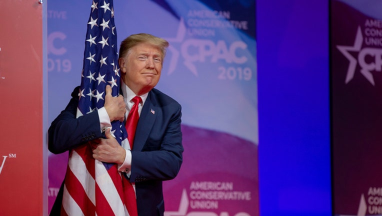 bb539427-GETTY Trump hugging a flag at CPAC on March 2, 2019-404023