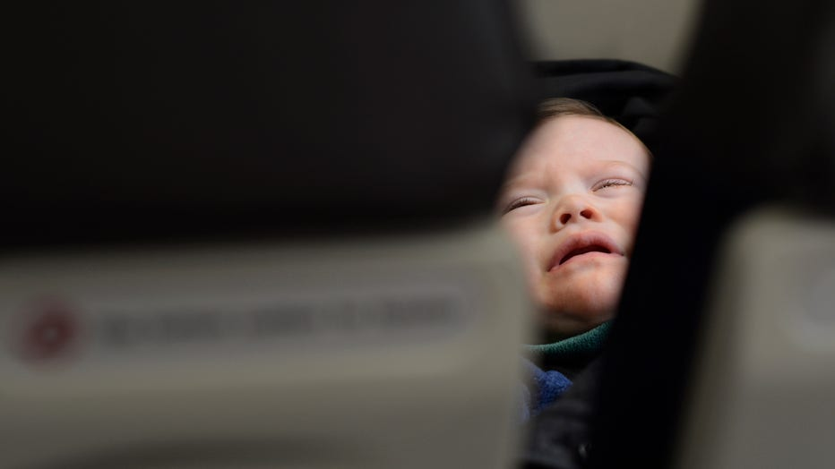 A file image shows a toddler crying in the seat beside his mother as they fly in a passenger jet departing from Dallas/Fort Worth International Airport. (Photo by Robert Alexander/Getty Images)