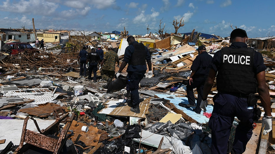 Members of the police join a recovery team looking in the debris in Marsh Harbour, Bahamas one week after Hurricane Dorian. The search for bodies continues, and the death toll is expected to keep rising.
