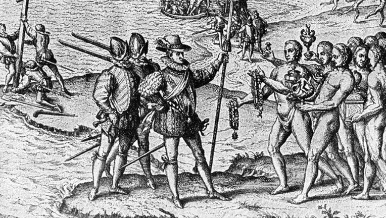 1492, Christopher Columbus lands on Watling Island and meets the natives, while three of his shipmates erect a cross.