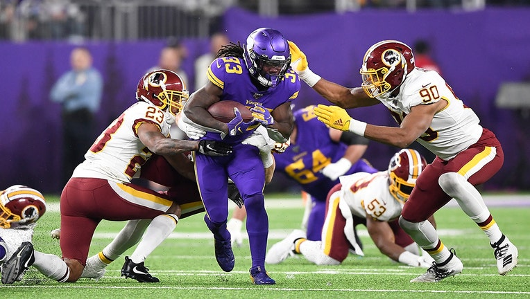 MINNEAPOLIS, MINNESOTA - OCTOBER 24: Running back Dalvin Cook #33 of the Minnesota Vikings runs against the defense of Montez Sweat #90 and Quinton Dunbar #23 of the Washington Redskins in the game at U.S. Bank Stadium on October 24, 2019 in Minneapolis, Minnesota. (Photo by Hannah Foslien/Getty Images)