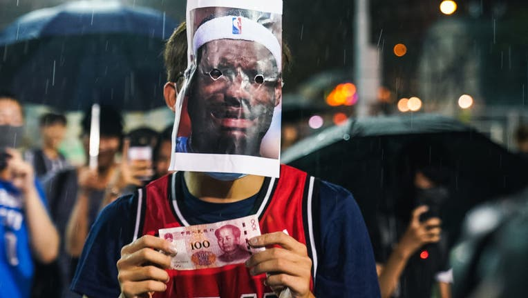 HONG KONG, CHINA: A basketball fan wearing Miami Heat jersey with a Lebron James mask on licking a 100 Chinese yuan bill on October 15, 2019 in Southorn Playground, Wan Chai, Hong Kong, China. Anti-government demonstrations in Hong Kong stretched into its fifth month after the Chinese territory's government invoked emergency powers earlier this month to introduce an anti-mask law. Protesters continue to call for Hong Kong's Chief Executive Carrie Lam to meet their remaining demands since the controversial extradition bill was withdrawn, which includes an independent inquiry into police brutality, the retraction of the word