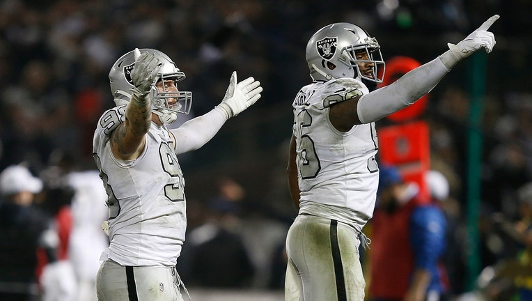 OAKLAND, CALIFORNIA - NOVEMBER 07: Maxx Crosby #98 and Clelin Ferrell #96 of the Oakland Raiders celebrate after an interception was thrown by Philip Rivers #17 of the Los Angeles Chargers late in the fourth quarter at RingCentral Coliseum on November 07, 2019 in Oakland, California. (Photo by Lachlan Cunningham/Getty Images)