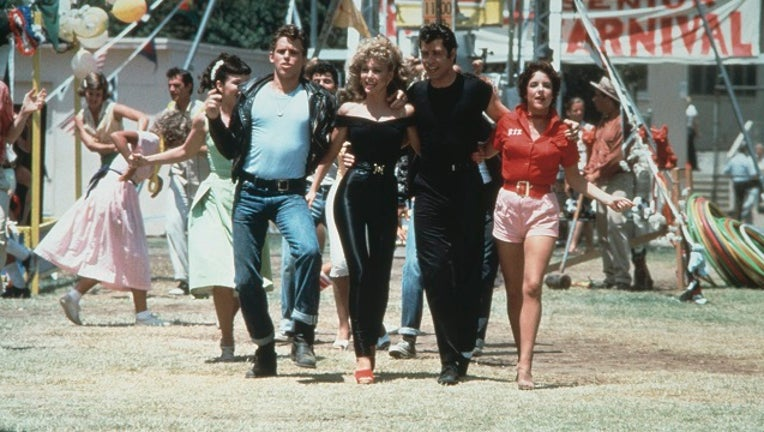Jeff Conaway, Olivia Newton-John, John Travolta and Stockard Channing walk arm in arm at a carnival in a still from the film, 'Grease.'