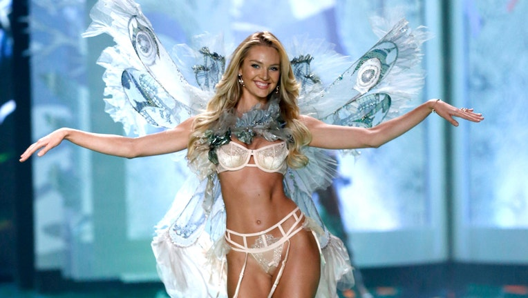 Model Candice Swanepoel wears Victoria's Secret Designer Collection Bra, Garter Belt and Matching Panty with Swarovski crystals, Hand Dyed Tulle and Chiffon Wings and Neck Piece on the runway at the 2014 Victoria's Secret Runway Show - Swarovski Crystal Looks at Earl's Court Exhibition Centre on December 2, 2014 in London, England. (Photo by Tristan Fewings/Getty Images for Swarovski)