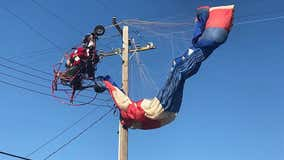 Paraglider dressed as Santa gets tangled in power lines while delivering candy canes