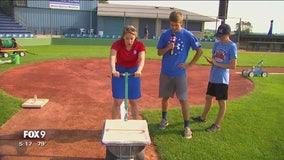 Fox 9 Meteorologist Jennifer McDermed chalks the field in Miesville