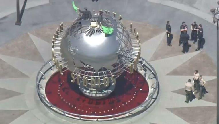 67a07e37-Activists-climb-globe-at-Universal-Studios_1555968163568-407068.jpg