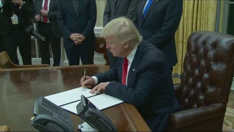trump signs executive order_1484962480687.JPG