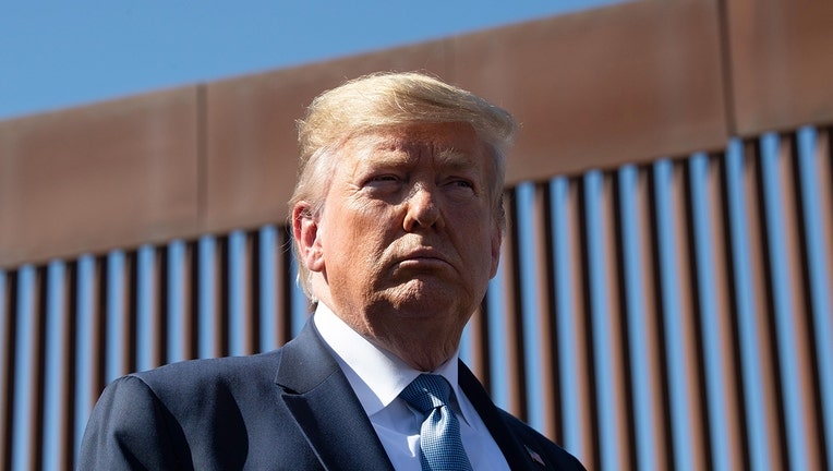 FILE -US President Donald Trump visits the US-Mexico border fence in California.