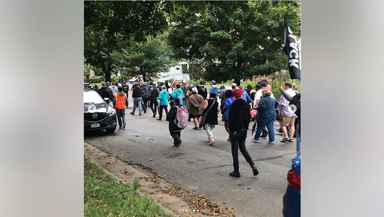 Protesters walk the Midway neighborhood