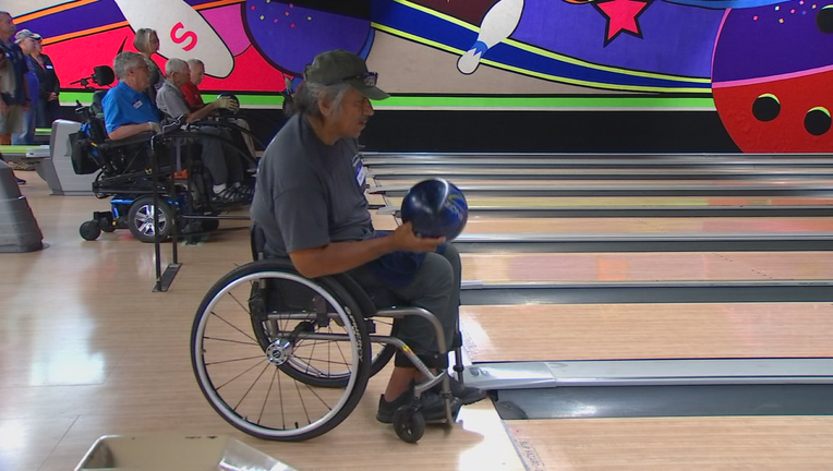 Man in wheelchair tosses bowling ball.