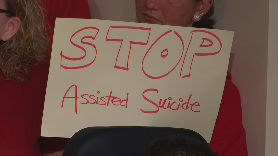 Opponents hold signs during protest against bill.