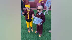 Boy wearing P.J. Fleck costume meets with coach on Gophers sideline
