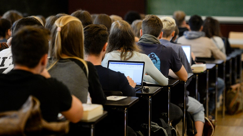 FILE - students sit in a lecture hall during a lecture.