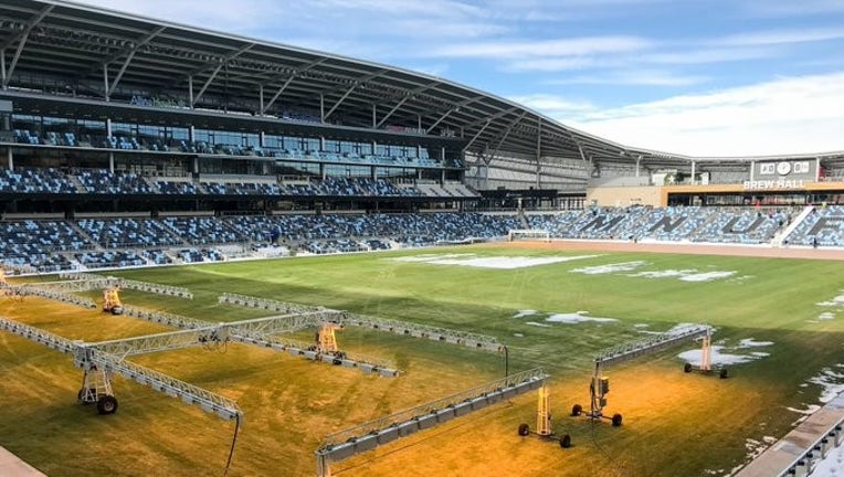 Heat lamps are used by Allianz Field staff to melt the snow and prepare the pitch for opening weekend.