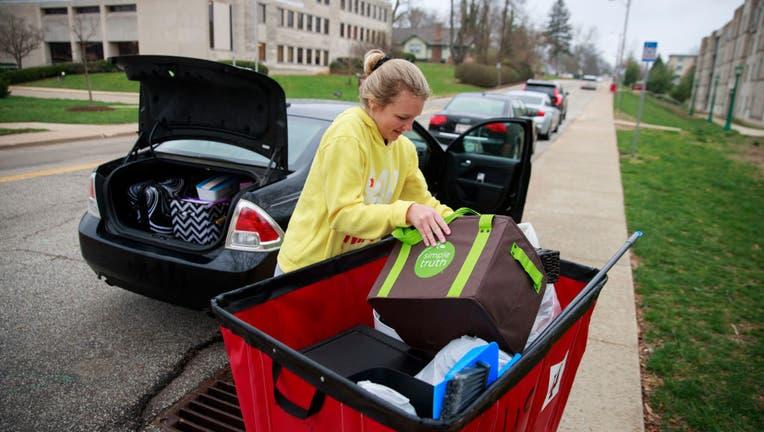 Indiana University freshman Ashley Follmer moves items from