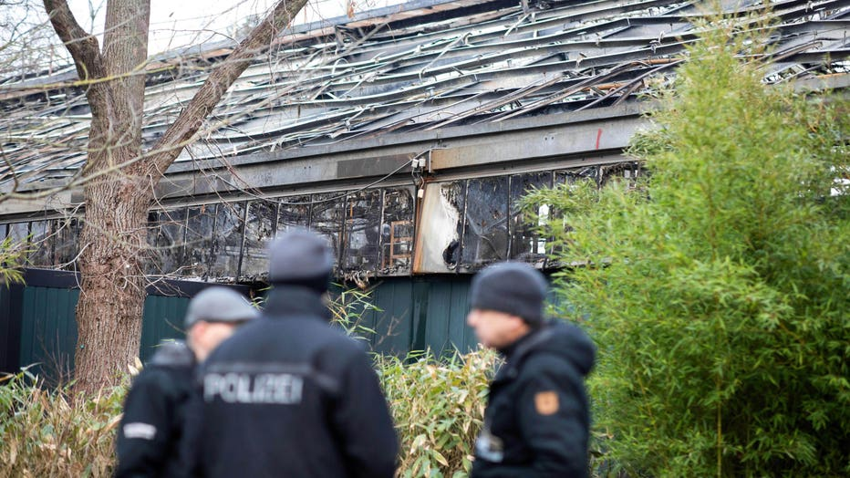 A picture taken on Jan. 2, 2020 shows police standing in front of the burned-out monkey house at Krefeld zoo in Germany after a fire on New Year's Eve, killed dozens of animals, including orangutans, chimpanzees and marmosets. (Photo by Marcel Kusch / dpa / AFP) / Germany OUT (Photo by MARCEL KUSCH/dpa/AFP via Getty Images)