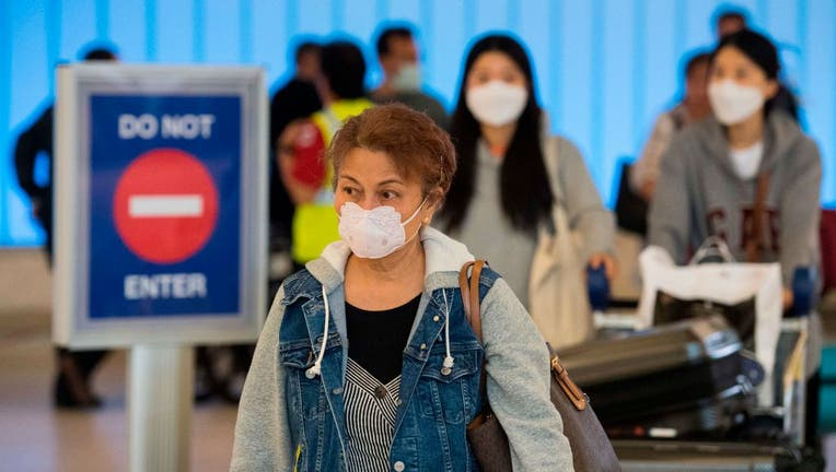 Passengers wear face masks to protect against the spread of the COVID-19, coronavirus, as they arrive at LAX airport in Los Angeles, California on Feb. 29, 2020.