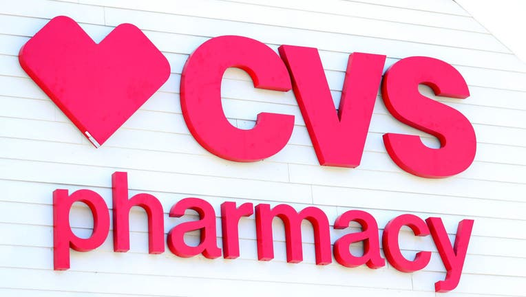 FILE - A sign on the side of the CVS Pharmacy on May 15, 2020 in Carver, Massachusetts. Nine CVS locations began providing coronavirus tests in Massachusetts, issuing self swab tests to people by appointment.