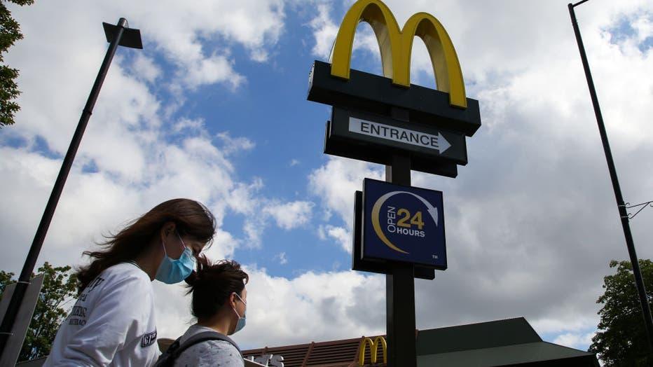 Women wearing face masks walks past a McDonald's logo