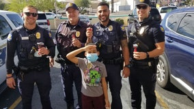 Boy gifts officers candy with toy police cars on top to show appreciation