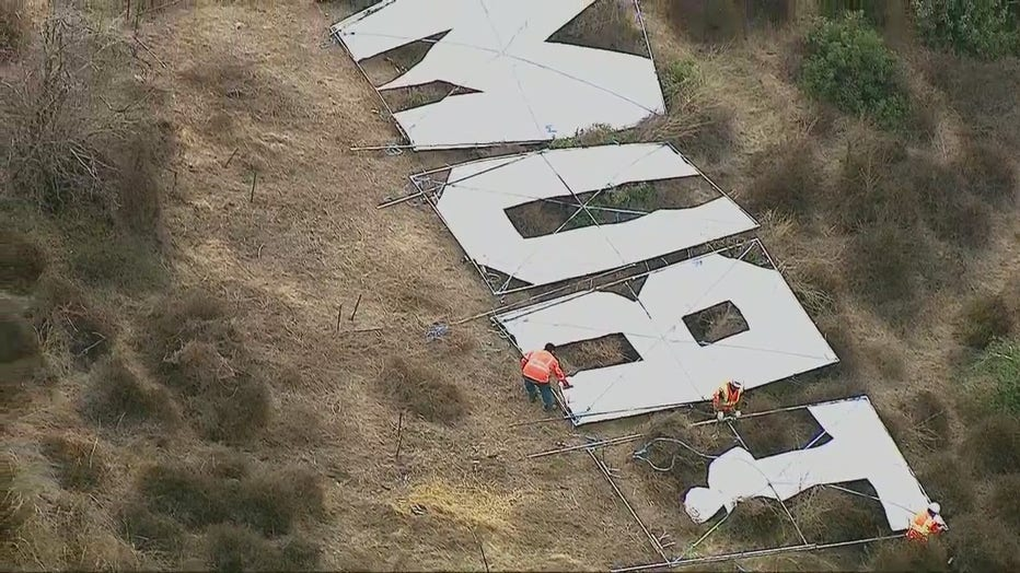 A large sign that read 'Trump' being removed from the hillside next to the 405 Freeway