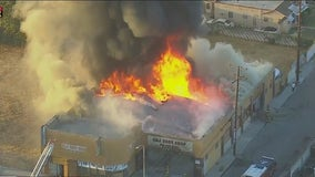 Commercial building fire engulfs auto body shop in Compton