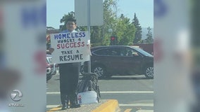 Homeless man holds sign 'Hungry For Success', hands out resume