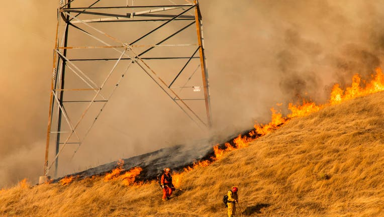 TOPSHOT - Firefighters set a back fire along a hillside near PG&E power lines during firefighting operations to battle the Kincade Fire in Healdsburg, California on October 26, 2019. - US officials on October 26 ordered about 50,000 people to evacuate parts of the San Francisco Bay area in California as hot dry winds are forecast to fan raging wildfires. (Photo by Philip Pacheco / AFP) (Photo by PHILIP PACHECO/AFP via Getty Images)
