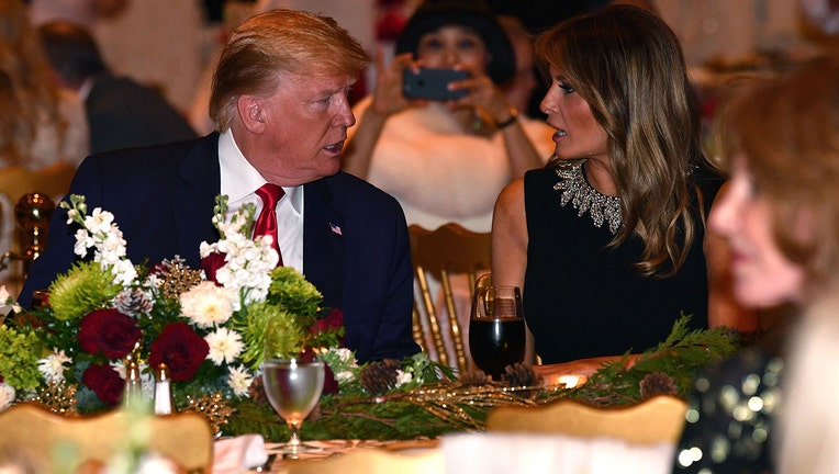 US President Donald Trump and First Lady Melania Trump attend a Christmas Eve dinner with his family at Mar-A-Lago in Palm Beach, Florida on December 24, 2019.