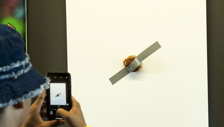 "The piece, officially named ""The Sandwich,"" is listed at $120,003.99 and is being described as ""a mixed media work of art consisting of a toasted brioche bun, two pickles, fried chicken, mayo and duct tape over a canvas."""