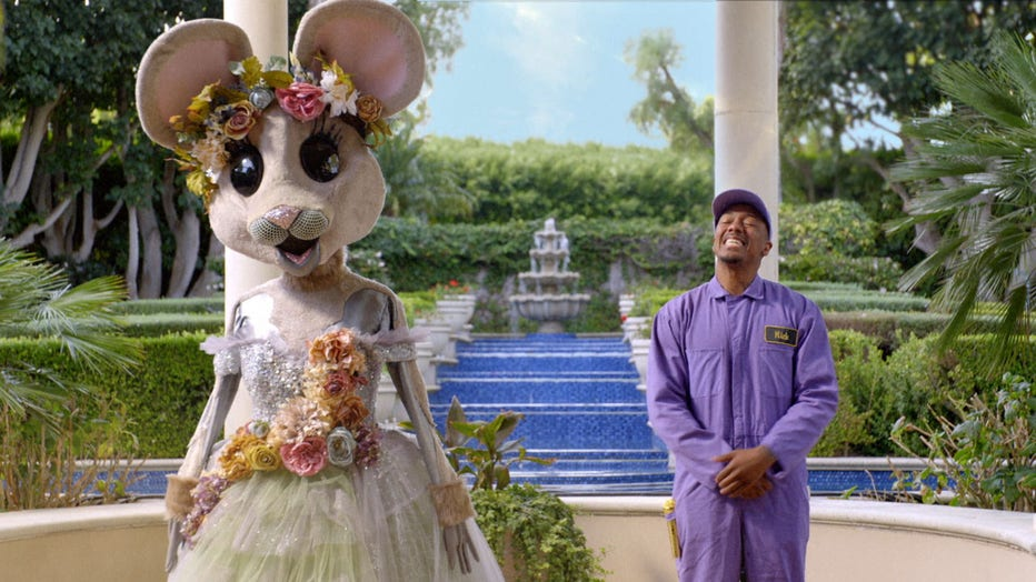 """The Masked Singer"" host Nick Cannon is pictured delivering a mouse costume to a mystery celebrity in a teaser clip of season 3. (Photo credit: FOX)"