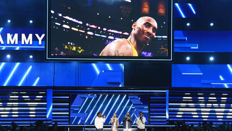 LOS ANGELES, CALIFORNIA - JANUARY 26: An image of the late Kobe Bryant is projected onto a screen while host Alicia Keys (2nd from L) and (from L) Nathan Morris, Wanya Morris, and Shawn Stockman of music group Boyz II Men perform onstage during the 62nd Annual GRAMMY Awards at STAPLES Center on January 26, 2020 in Los Angeles, California. (Photo by Kevin Winter/Getty Images for The Recording Academy )
