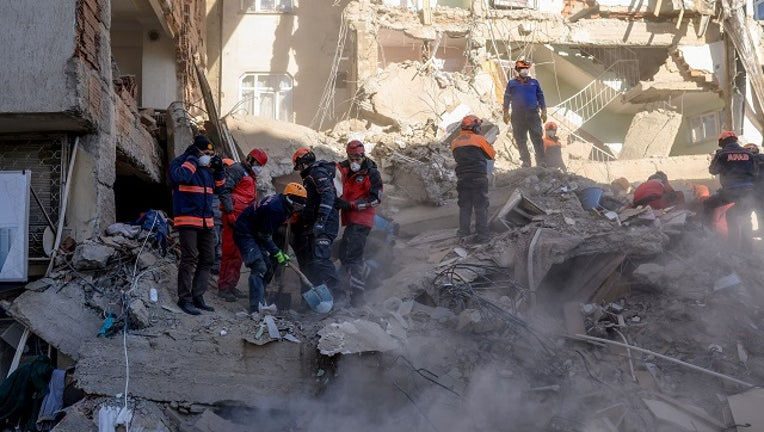 Rescue workers work amid the rubble of a building after an earthquake in Elazig, eastern Turkey, on January 25, 2020. The magnitude 6.8 quake struck in the evening of January 24.