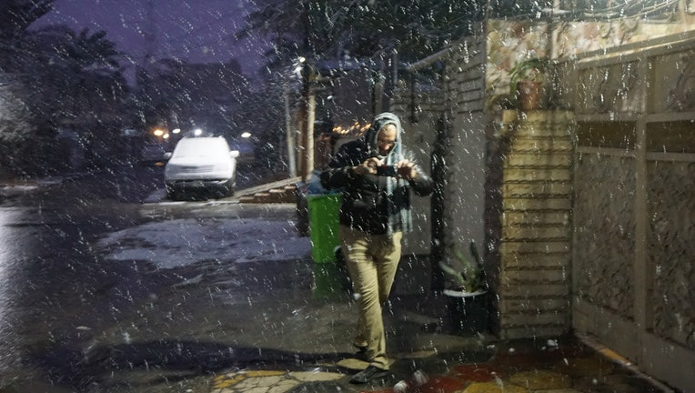 An Iraqi man takes pictures with his smart phone during snow fall early on February 11, 2020 in Baghdad, as the Iraqi capital woke up covered in a thin layer of fresh snow, an extremely rare phenomenon for one of the world's hottest countries. - The last recorded snowfall in the city was in 2008, but it was a quick and mostly slushy affair -- and prior to that, it had been a century since Baghdad saw any flakes. (Photo by SABAH ARAR / AFP) (Photo by SABAH ARAR/AFP via Getty Images)