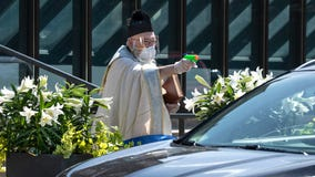 Priest uses squirt gun to shoot holy water and maintain social distancing