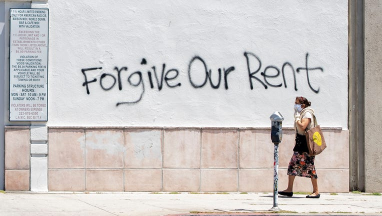 A woman wearing a mask walks past a wall bearing graffiti asking for rent forgiveness on La Brea Avenue amid the COVID-19 pandemic on May 1, 2020, in Los Angeles, California.